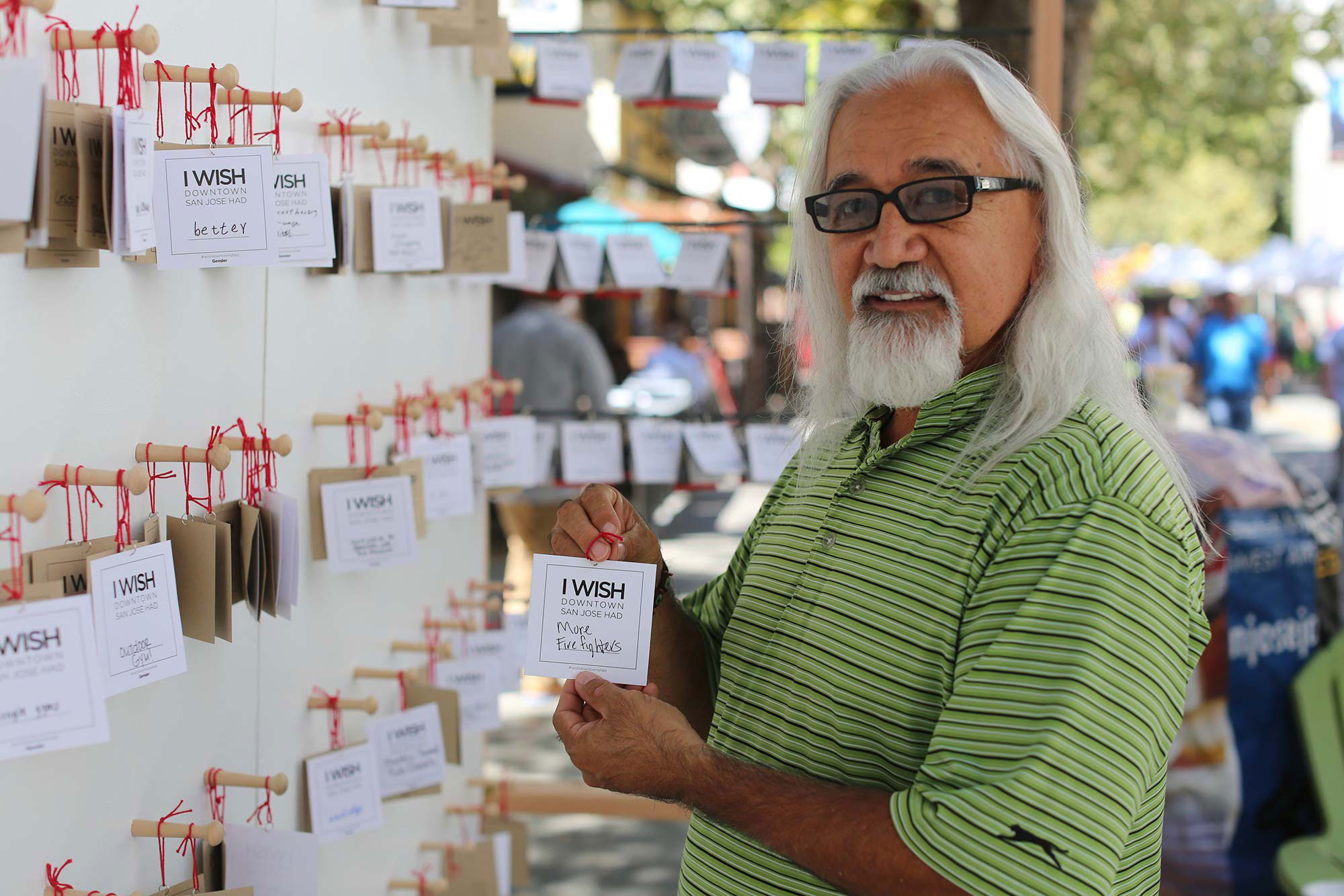 "Man holding a notecard that reads ""I wish San Jose had more firefighters"" in front of an outdoor wall with similar notecards and wishes."