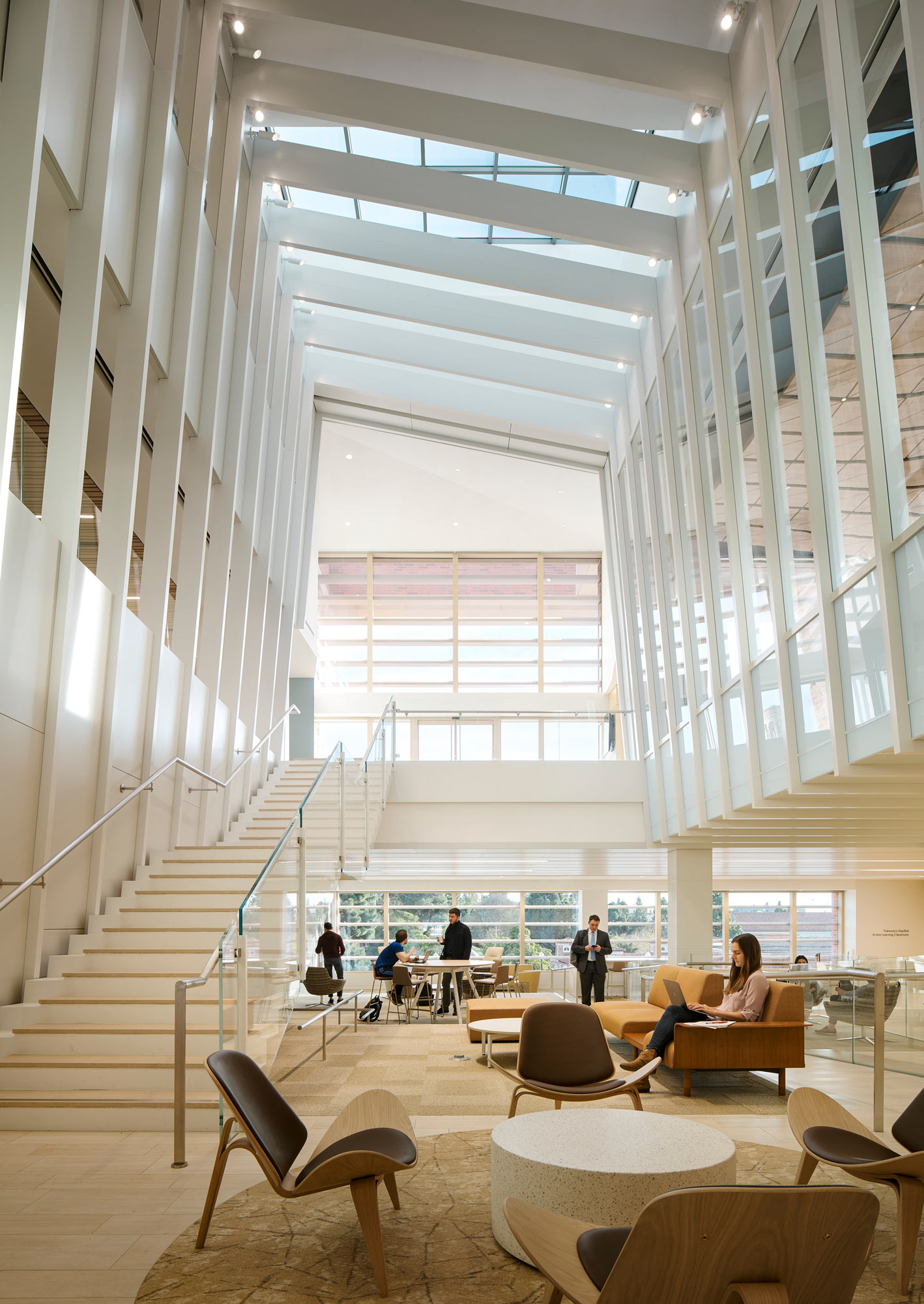 People sitting, working, and studying on furniture in the atrium of an academic building.