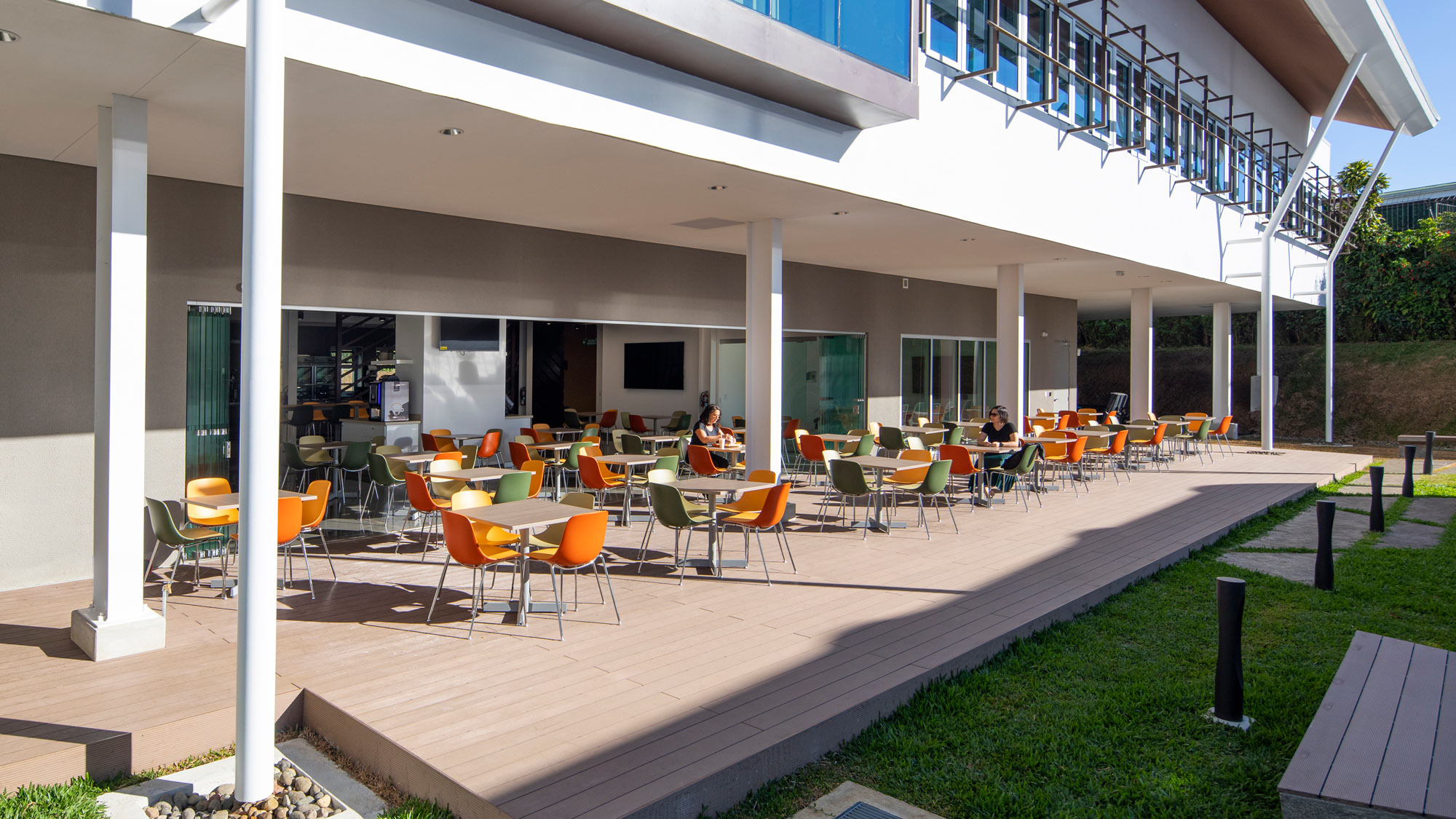 A photograph of an open-air office cafeteria with colorful seating on a patio bordered by green grass.